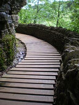 A boardwalk trail winds beside a rock face.
