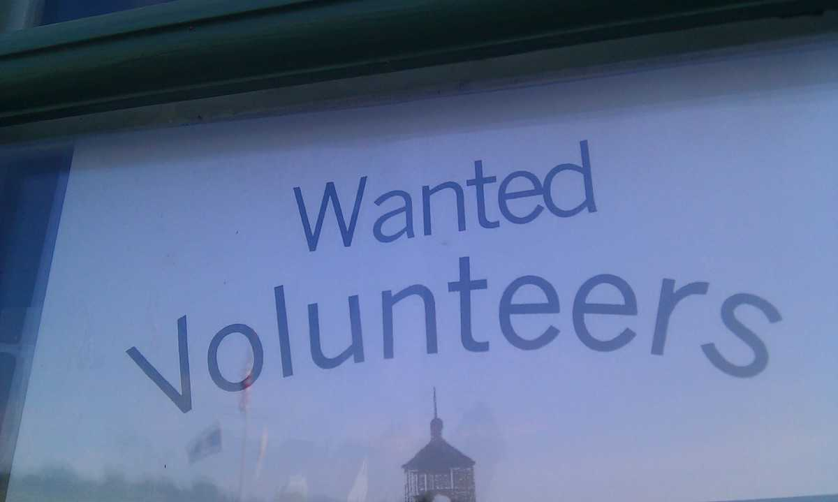 "Sign in a window says, ""Wanted: Volunteers."""