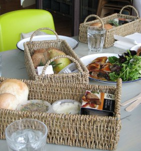 Baskets filled with picnic fare: Rolls, goat cheese, pate, quince paste, various spreads, and pheasant terrine.