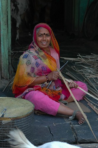 A brightly-dressed woman weaving a basket.