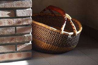 In a home, a basket sits in the sunlight.