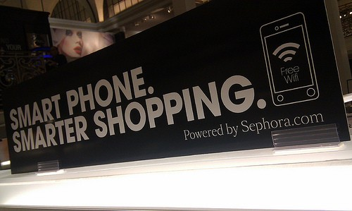 """Sign in a retail store says, """"Smart phone, smarter shopping. Free wifi."""""""
