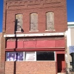 A downtown brick building with boarded up windows.