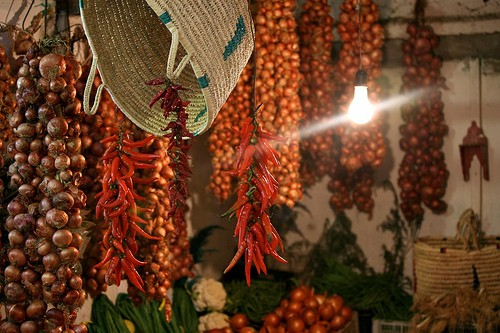 Strings of chili peppers and a basket hanging in a small shop.