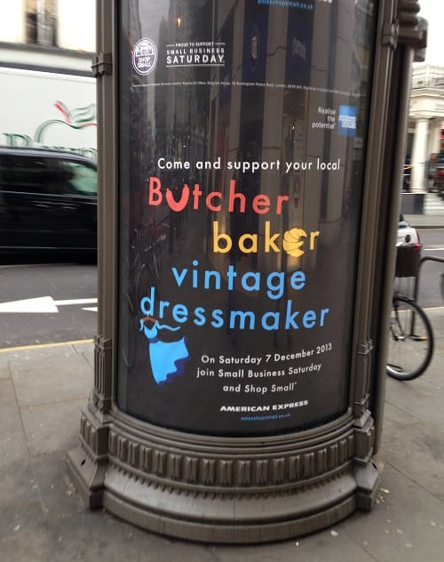 "Outdoor advertising banner says, ""Come and support your local butcher, baker and vintage dressmaker."""