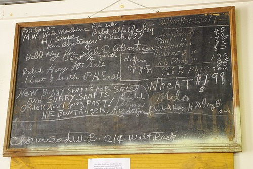 A chalk board with local farm and community announcements on it.