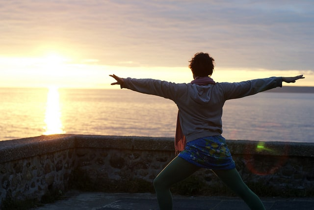 Woman doing yoga in front of the sunrise over the ocean.