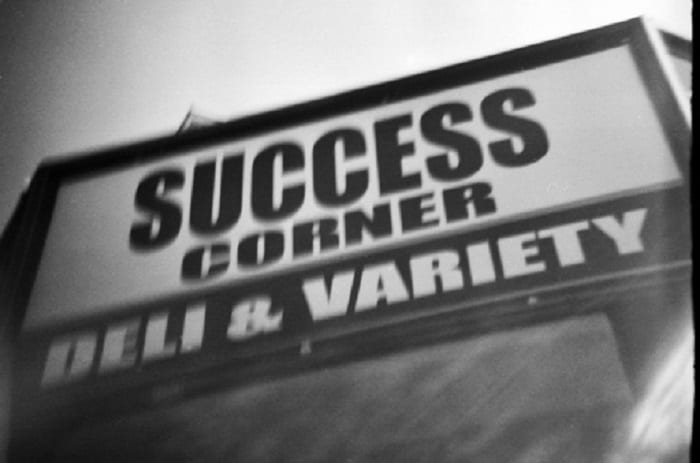"Sign says, ""Success Corner Deli and Variety."""