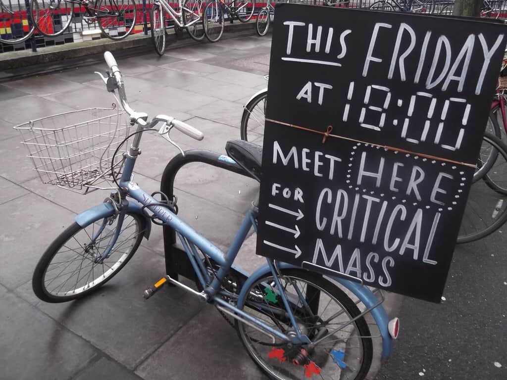 "Bike with a basket carrying a sign that says ""This Friday, meet here for critical mass."""