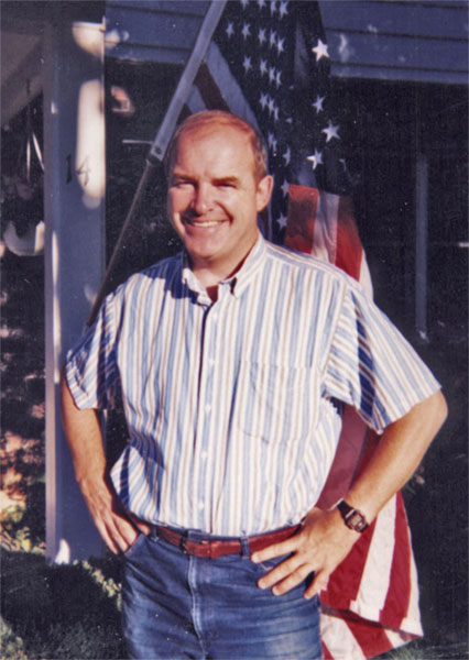 Mike Cronin standing in front of a USA flag