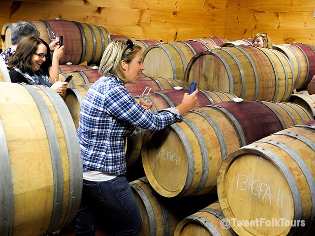 Smiling women are tweeting pictures from a room full of wine barrels.