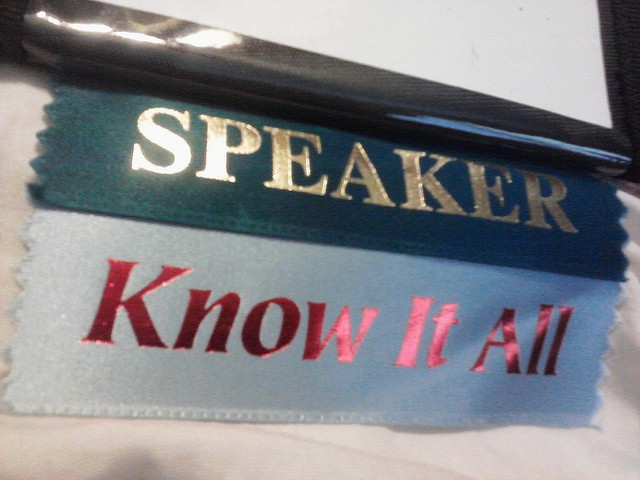 "Ribbons on a name tag read, ""Speaker. Know-it-all."""