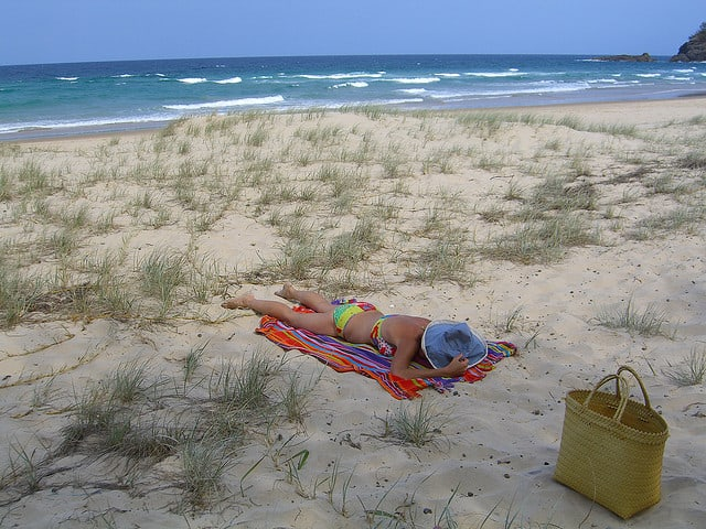 Woman sunning on the beach with a basket.