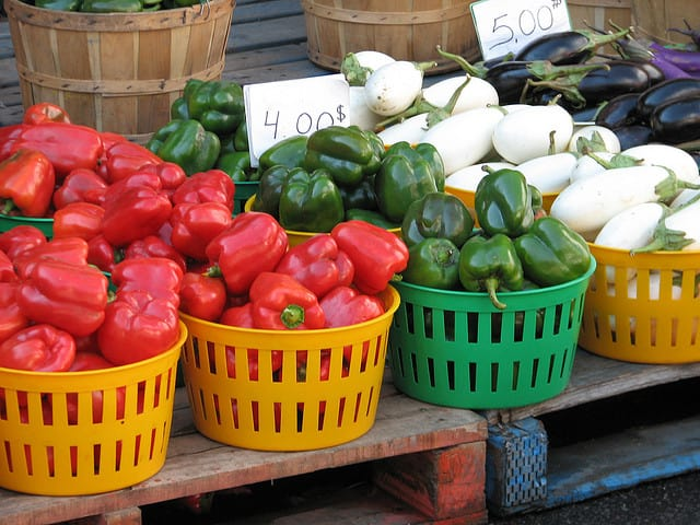 Baskets of red and green peppers in a market place.