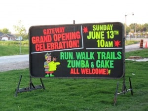 Business sign for a grand opening includes zumba and cake.
