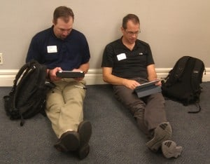 Two people seated on the floor, using iPads to work.