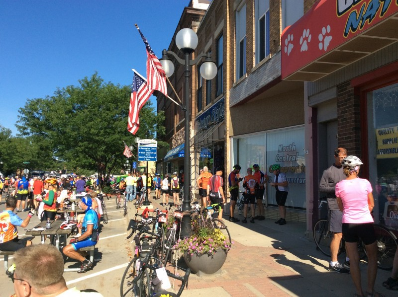 What can a business do when downtown is packed full of people who aren't shopping for what you sell? RAGBRAI cyclists in downtown Webster City, Iowa. Photo by Deb Brown, used by permission.