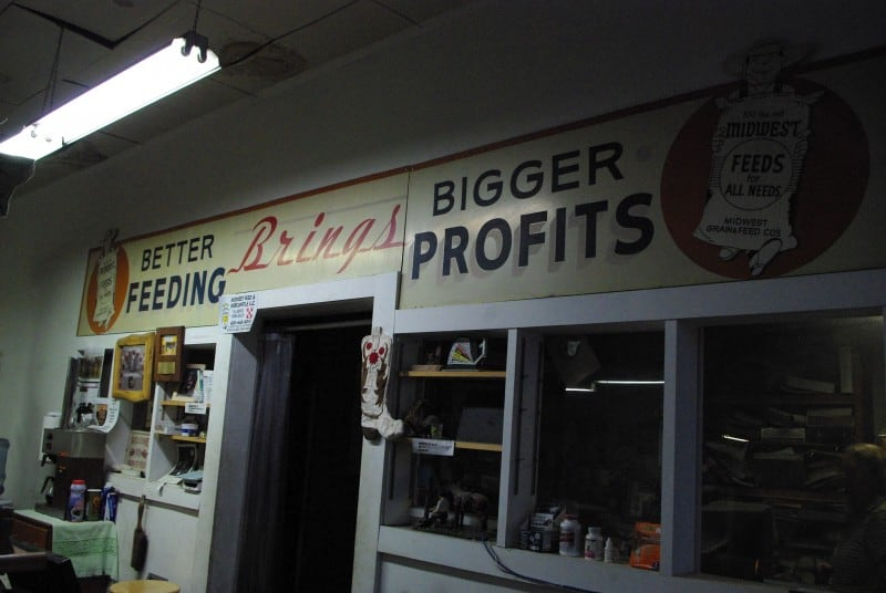 "A sign in an old-fashioned feed store says ""better feeding brings bigger profits"""