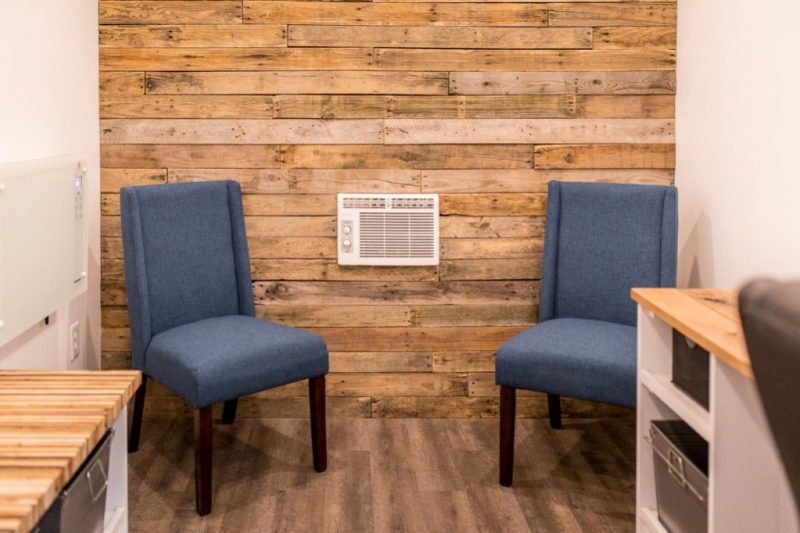 Two side chairs in the tiny office, in front of an all-wood paneled wall.
