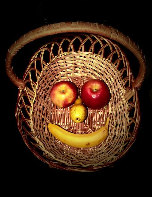 Basket with happy face made of fruit