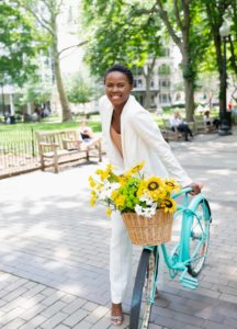 Woman with a bicycle basket of bright flowers