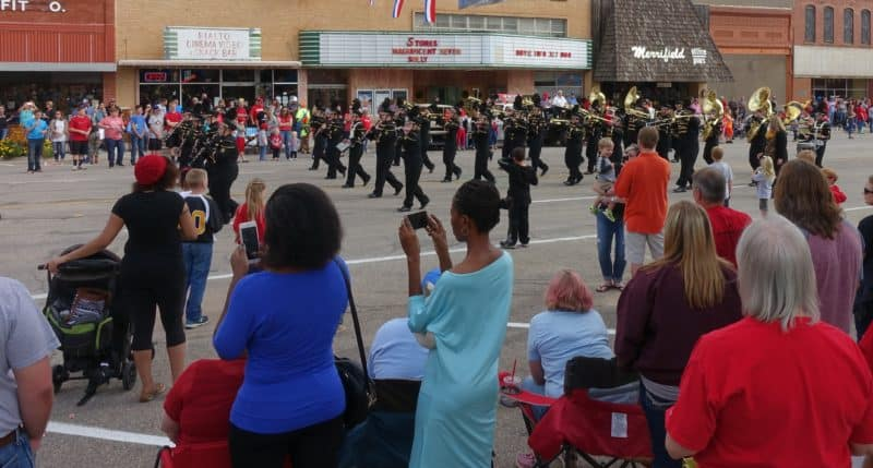 A diverse crowd watches a marching band in a small town parade