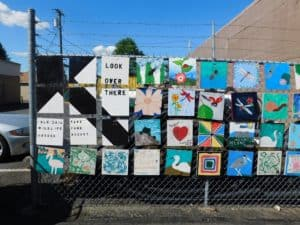 Art squares hanging on the chain link fence in neat rows.