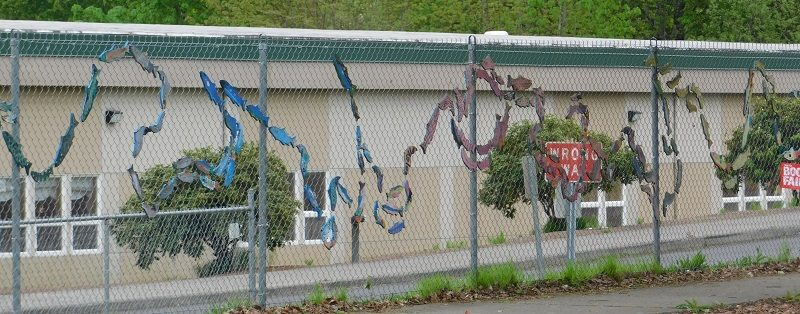 Painted fish shapes hang from a chain link fence