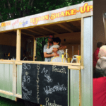 Kettle corn being sold from a stand in a yard, from a mobile trailer and from a coffee shop