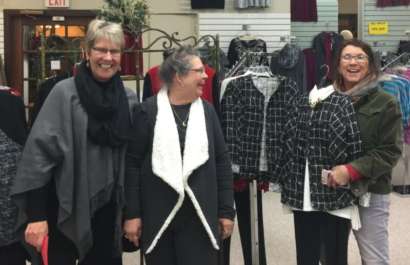 Three happy women stop and smile in a clothing store.
