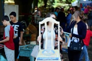 A woman carries an up-cycled chair she bought at Junque Fest surrounded by a diverse crowd