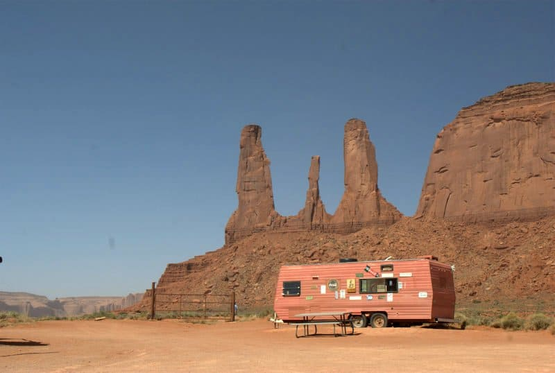 Near the iconic sandstone towers in Monument Valley, a concession trailer offers food, with a picnic table out front.